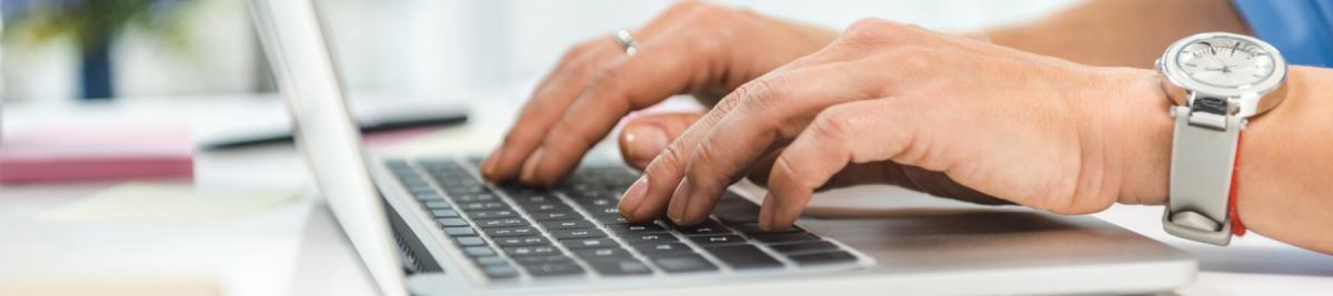 cropped view of businesswoman typing in laptop